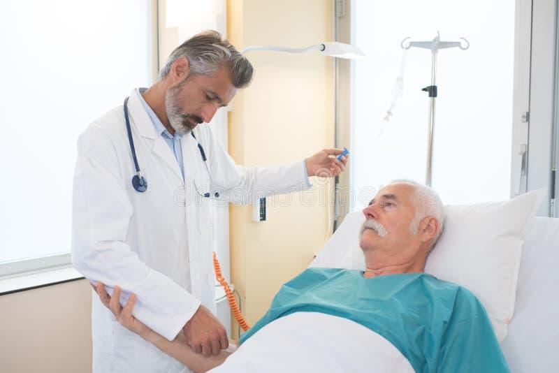 调整患者iv的护士 免版税库存照片