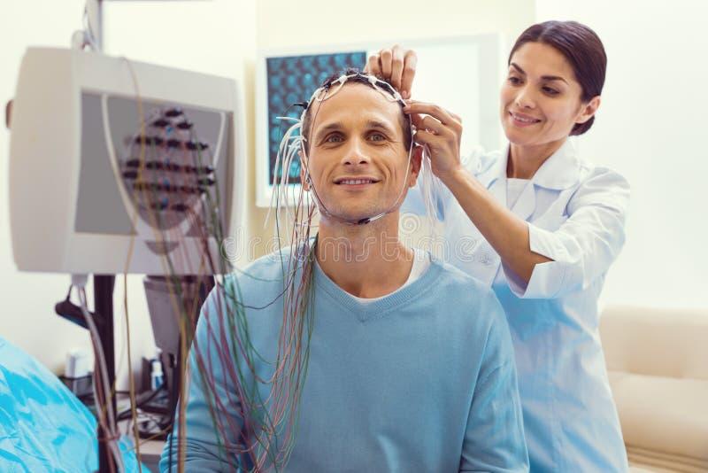 调整电极的快乐的医生在脑波记录仪分析前 图库摄影