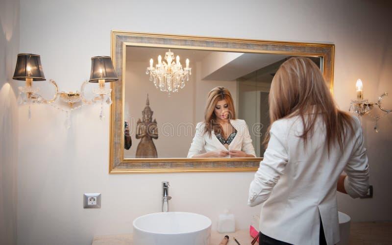 调查一个大镜子的办公室成套装备的肉欲的端庄的妇女。美丽和性感的白肤金发的少妇佩带的夹克 库存图片