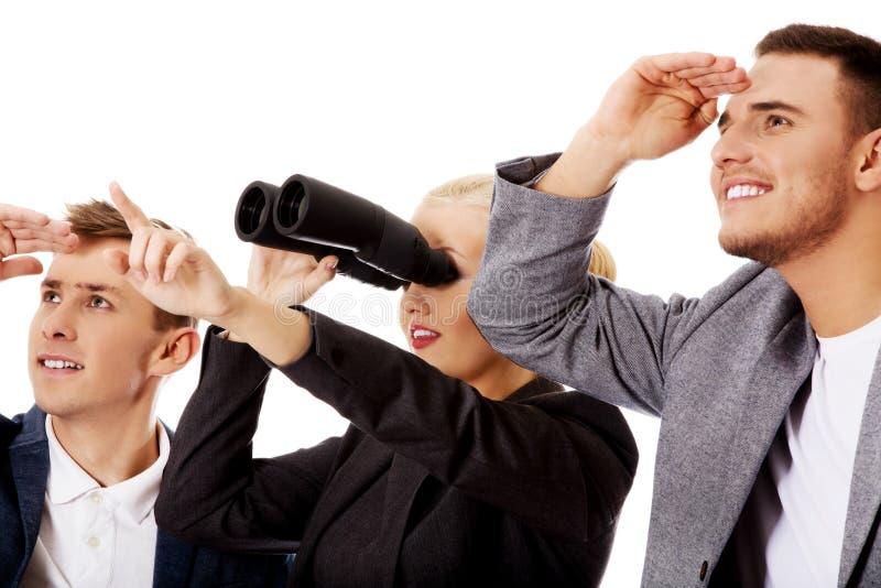 调查一名方向妇女的企业队使用双筒望远镜 免版税图库摄影
