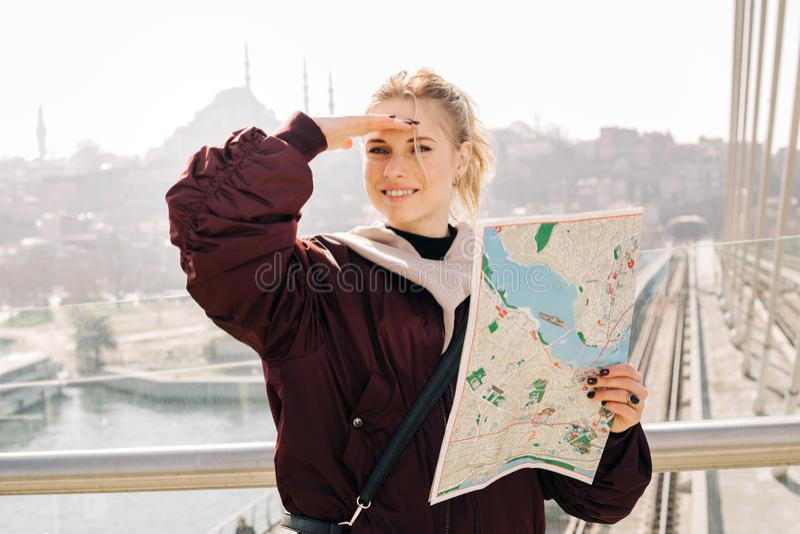 调查与地图的距离的愉快的白肤金发的妇女在她的手上由窗口 图库摄影