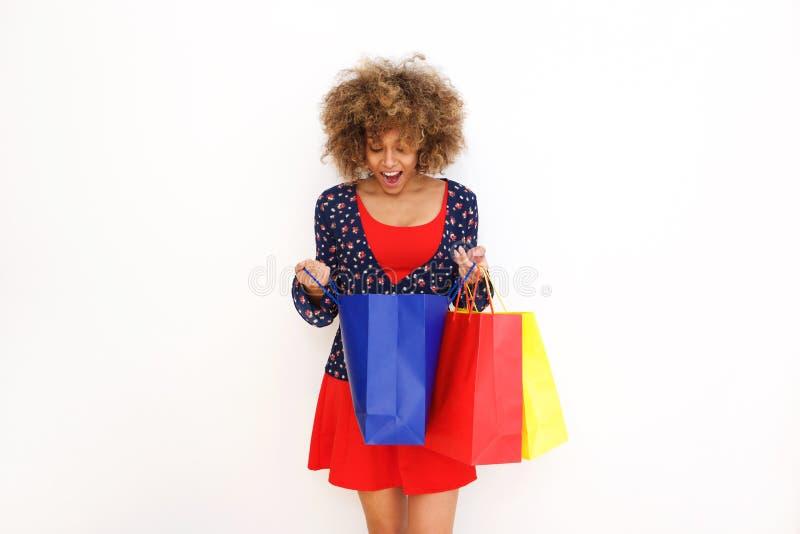 调查与惊奇的表示的购物袋的美丽的非裔美国人的女孩在面孔 免版税图库摄影