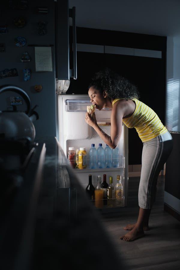 调查冰箱的黑人妇女为夜宵 库存图片