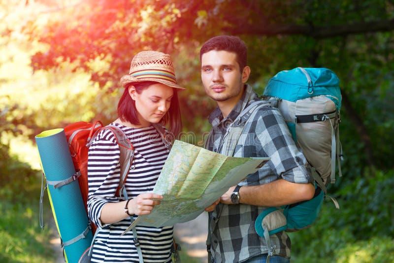 调查在森林足迹的地图的年轻远足者 免版税库存图片