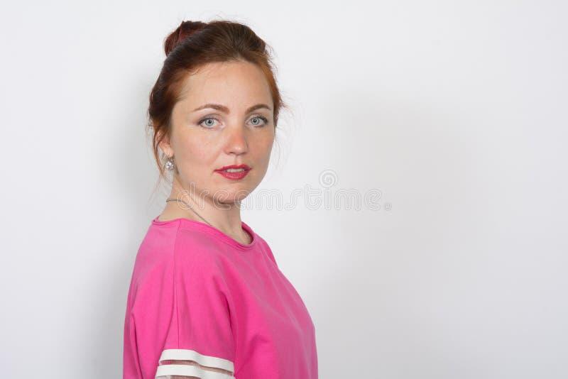 调查在白色背景的照相机的红发美丽的严肃的妇女的画象 免版税库存图片