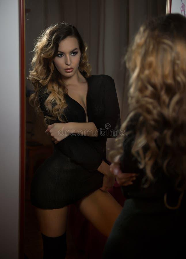 调查大墙壁镜子的黑成套装备的少妇 摆在镜子前面的美丽的卷曲公平的头发女孩 免版税图库摄影