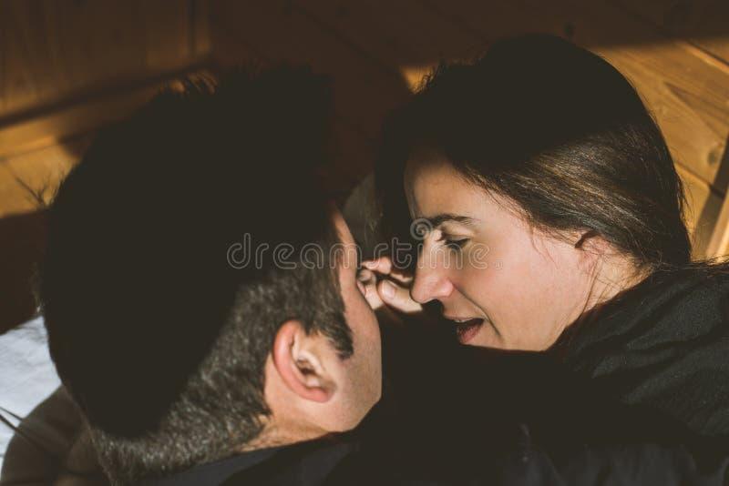 调查彼此的眼睛的一对愉快的年轻夫妇的画象 幸福和爱的概念在夫妇之间 库存照片