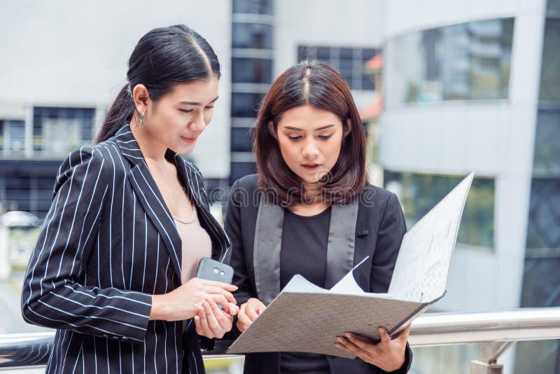 调查文件文件夹的两名年轻女实业家为分析赢利循环或销售收支相抵以后指向 免版税库存图片
