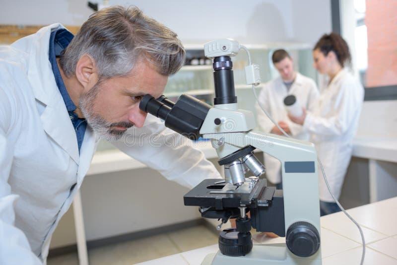 调查显微镜的高级技术员 库存照片