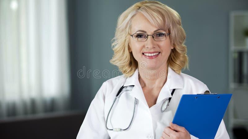 调查照相机的友好和微笑的夫人医生,给希望为补救 免版税库存图片