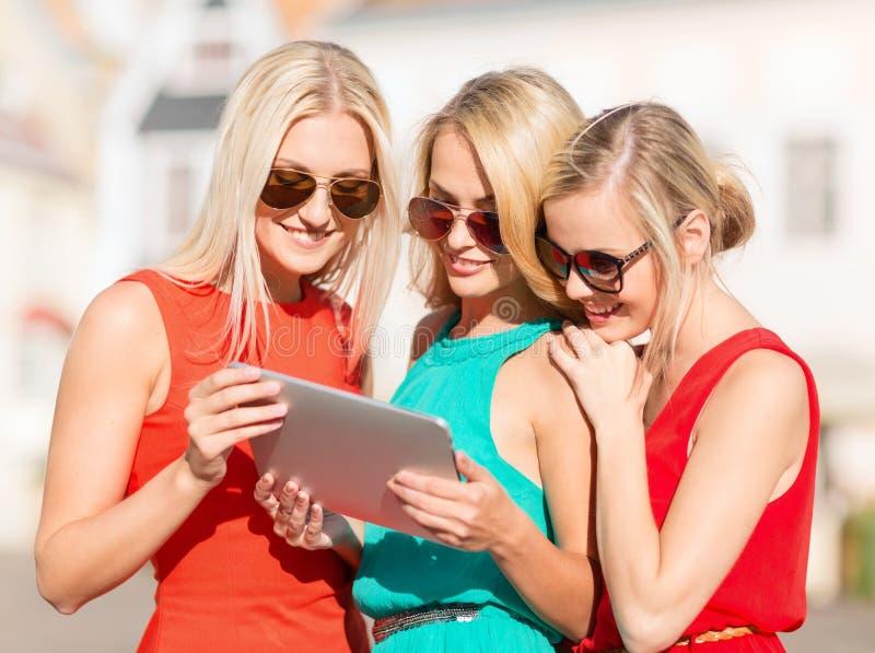 调查片剂个人计算机的美好的女孩toursits 免版税库存图片