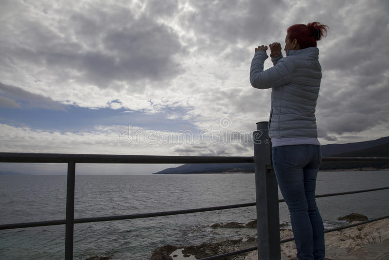 调查虚构的双筒望远镜的妇女 免版税库存图片