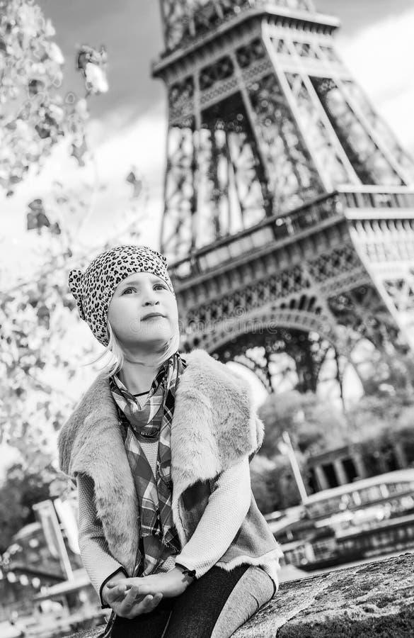 调查距离的女孩,当坐栏杆在巴黎时 免版税库存图片