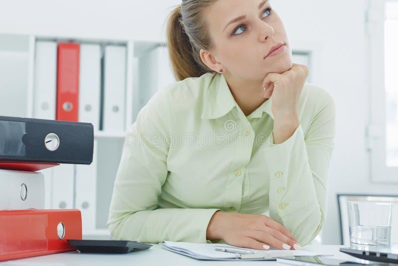 调查距离的疲乏的女实业家在堆文件夹旁边坐您的桌面 免版税库存照片