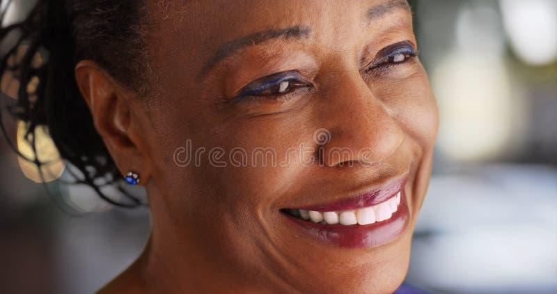 调查距离的一个年长黑人妇女的特写镜头 库存照片