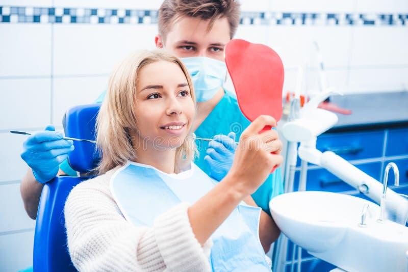 调查镜子的女孩和牙医 免版税图库摄影