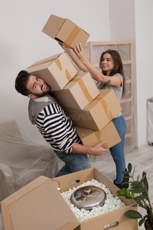 年轻调迁对新的公寓的人和妇女打开箱子 库存图片