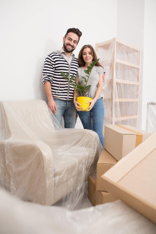 调迁,站立在与家具coverd的新的公寓的yong夫妇与箔 免版税库存图片