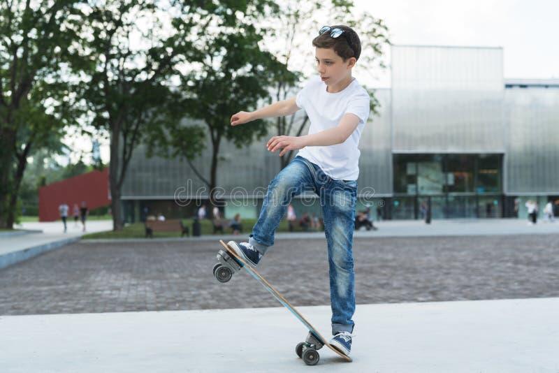 调遣结构树 男孩是在一件白色T恤杉打扮的少年,并且牛仔裤,滑冰,做欺骗 库存照片