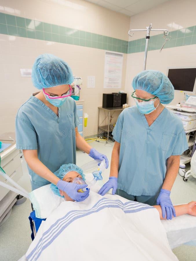 调整在女性患者的护士氧气面罩 库存照片