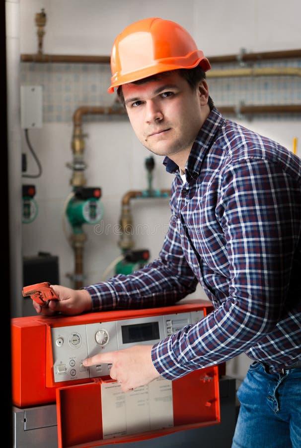 调整在控制板的年轻工程师系统工作 免版税库存图片