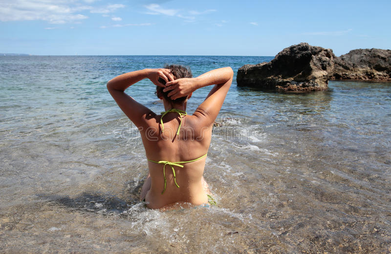 调整她的在海滩的女孩头发 库存图片