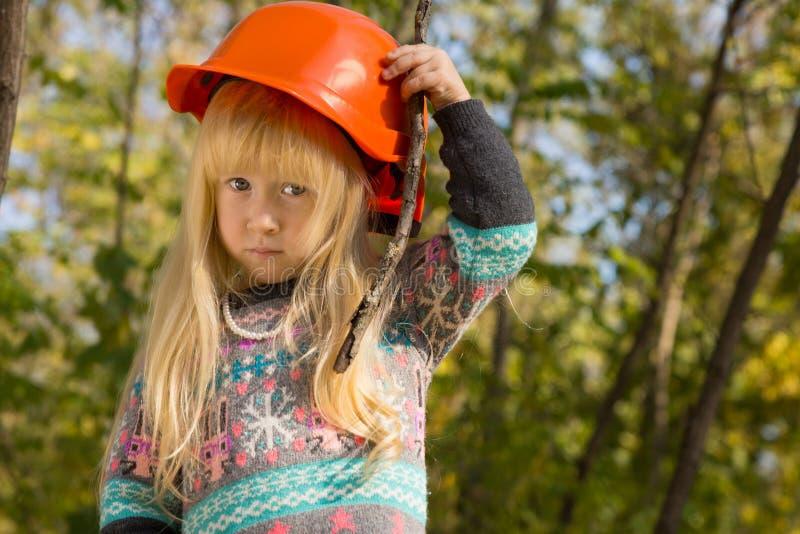 调整她的安全帽的逗人喜爱的小女孩 免版税库存照片
