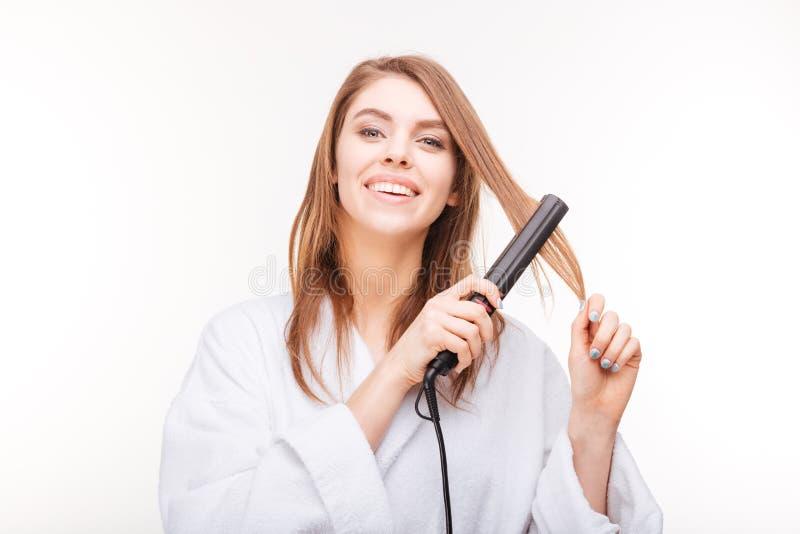 调直她的有直挺器的快乐的可爱的少妇头发 免版税库存照片