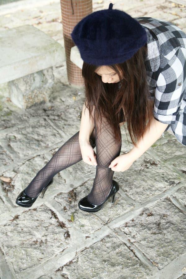 调整她的袜子的美丽的亚裔女孩 免版税库存照片