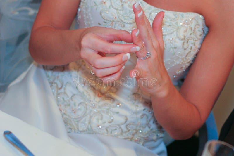 调整婚戒的新娘 免版税库存照片