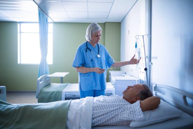 调整男性患者s iv滴水的护士 免版税库存照片