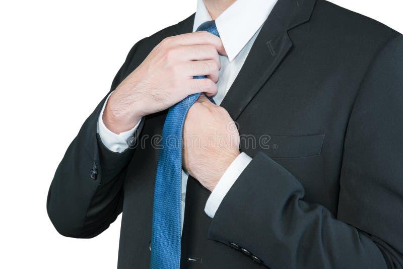 调整他的脖子关系的穿着体面的商人 免版税库存照片