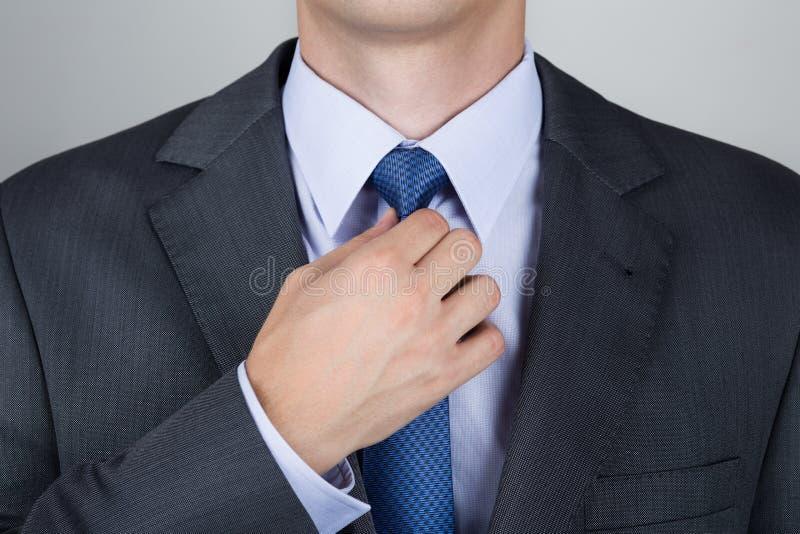 调整他的脖子领带的商人 库存图片
