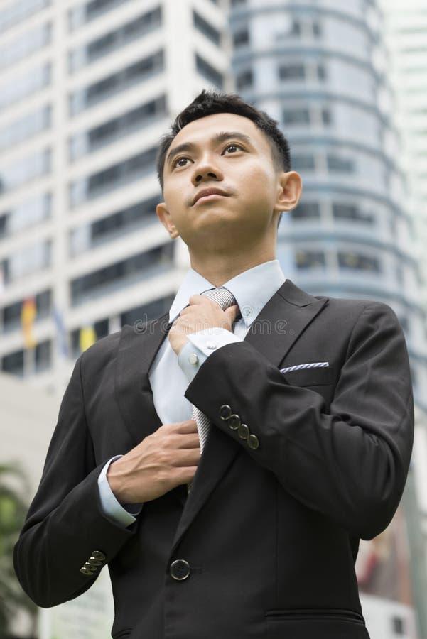 调整他的脖子领带的穿着体面的亚裔商人 库存图片