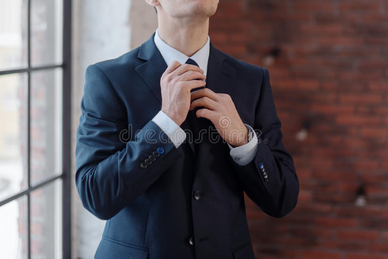 调整他的领带的商人特写镜头站立在办公室 库存图片