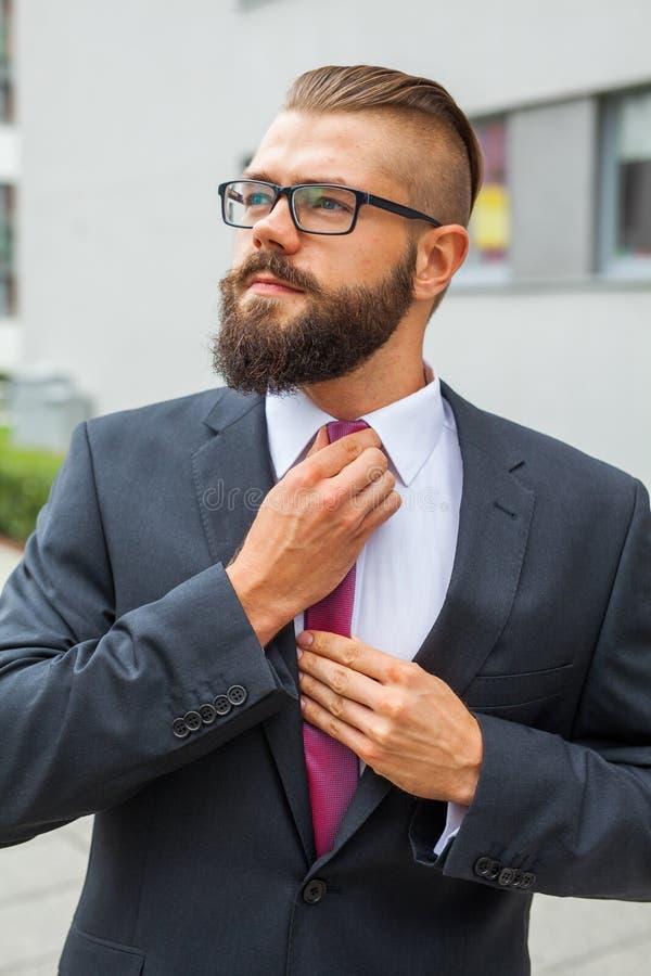 调整他的年轻可爱的商人领带 室外照片 库存图片