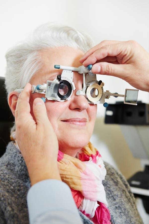 调整试验框架的眼镜师为 免版税库存照片