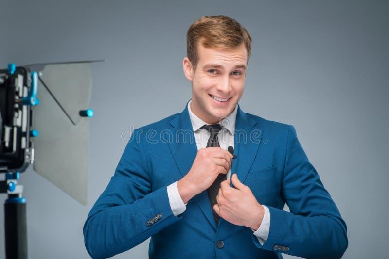 调整话筒的微笑的新闻记者 免版税库存照片