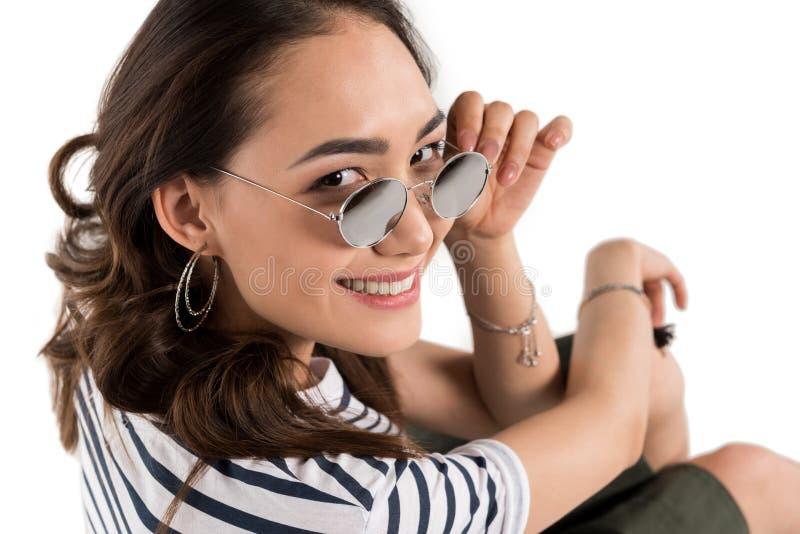 调整镜片和微笑对照相机的美丽的少妇 免版税库存照片
