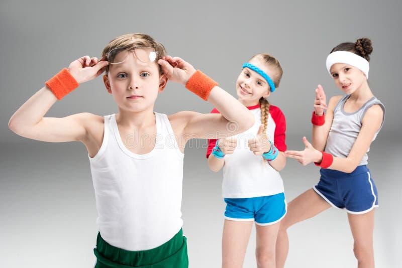调整镜片和运动的女孩的运动服的小男孩站立后边 免版税库存照片