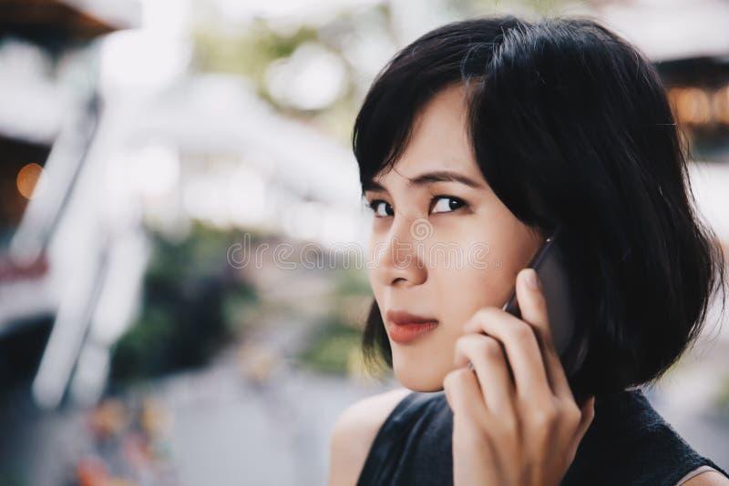 谈一名恼怒的亚裔的妇女她的在购物中心的手机 免版税图库摄影