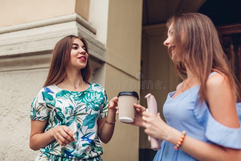 谈两名年轻美丽的妇女饮用的咖啡 女孩获得乐趣在城市 最好的朋友聊天户外 免版税库存照片