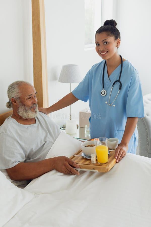 谈医疗保健的工作者在床上老人 免版税库存图片