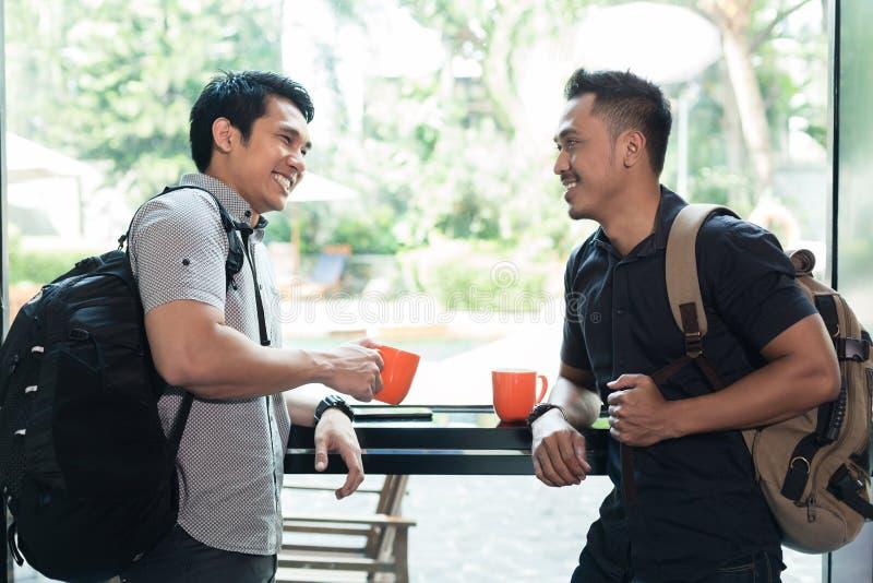 谈和喝咖啡的两个快乐的年轻人侧视图  免版税库存照片