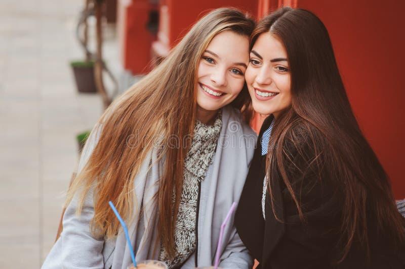 谈和喝咖啡的两个愉快的女朋友在咖啡馆的秋天城市 好朋友,年轻时兴的学生会议  图库摄影
