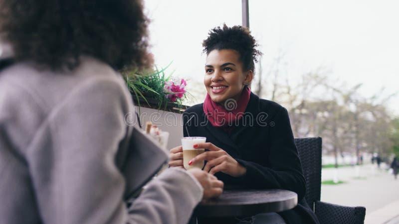 谈和喝在街道咖啡馆的两名可爱的混合的族种妇女咖啡 朋友获得乐趣在参观的购物中心销售以后 库存照片