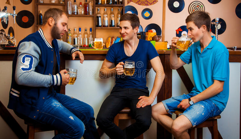谈和喝在酒吧的三个人啤酒 免版税库存照片