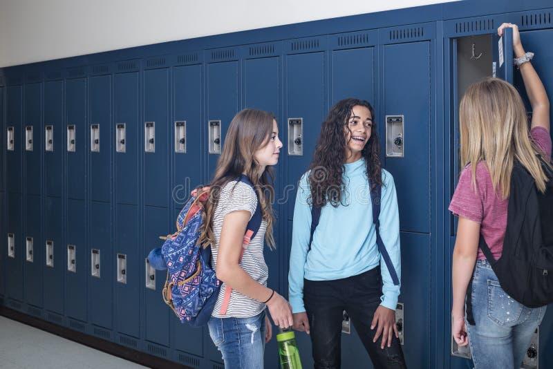谈和支持他们的衣物柜的初中学生在学校走廊 免版税库存照片