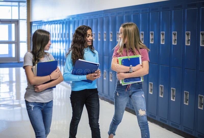 谈和支持他们的衣物柜的初中学生在学校走廊 免版税库存图片