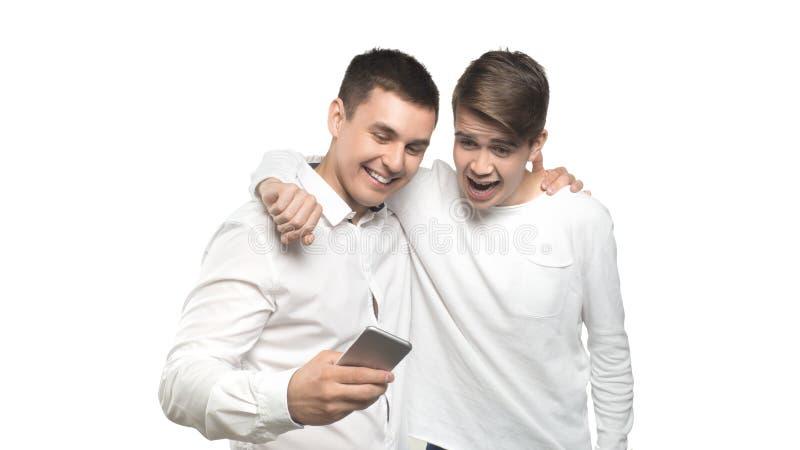 谈和看手机和笑的两个快乐的人,被隔绝在白色背景 库存图片